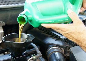 Close-up of hands of pouring engine motor oil in car engine.